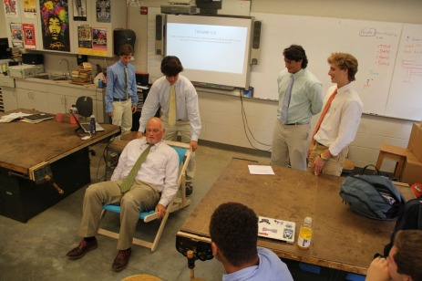 Mr. Heubeck tests a chair designed and built by design & woodworking students.